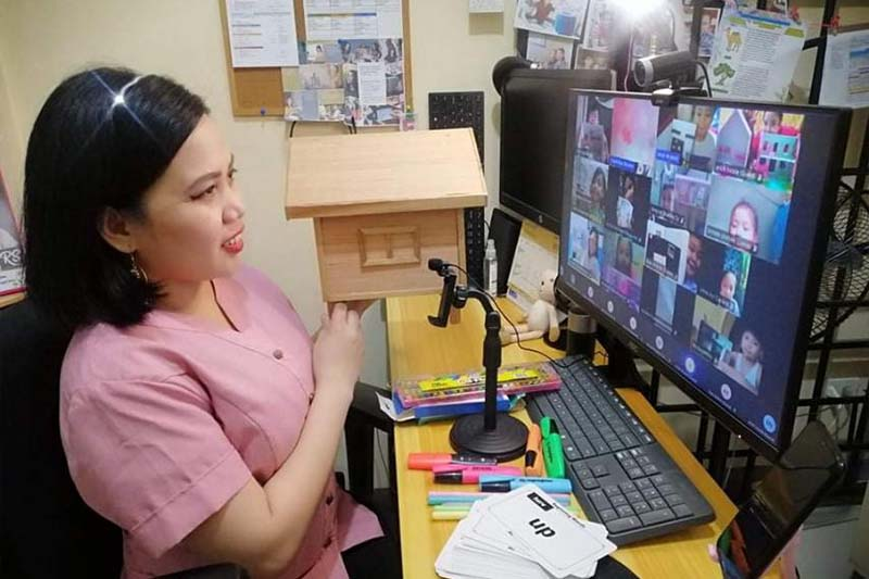 Ms. Sheila Mariano showing a sample of a house to her students  during distance learning using the LMS app